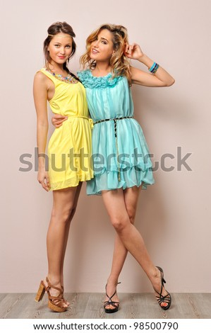 Two beautiful women in summer dresses. Studio  portrait. - stock photo
