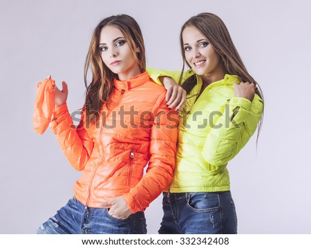 Two beautiful women in winter bright jacket in the Studio. Models in fashionable clothes on a light background - stock photo