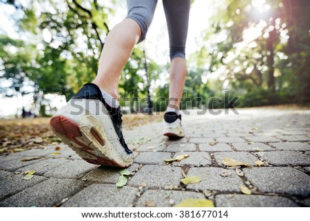 Two beautiful women jogging in park and keeping their bodies in shape - stock photo