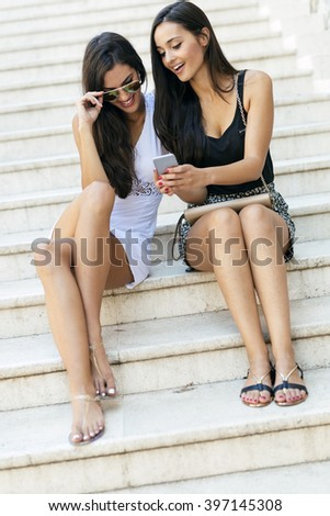 Two beautiful women looking at phone and smiling
