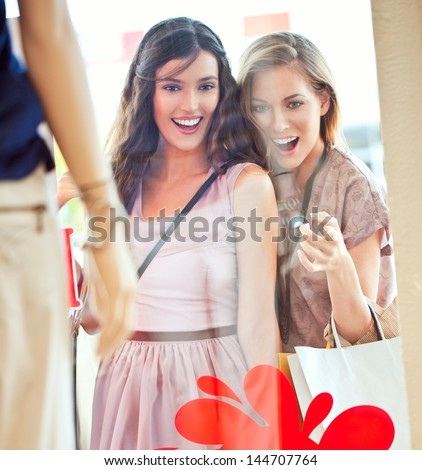Two beautiful women looking surprisedly at something in the clothing store window. - stock photo