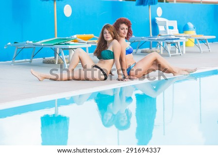 Two beautiful women next to swimming pool. They are on their twenties, wearing colourful bikini. Summer and lifestyle concepts.