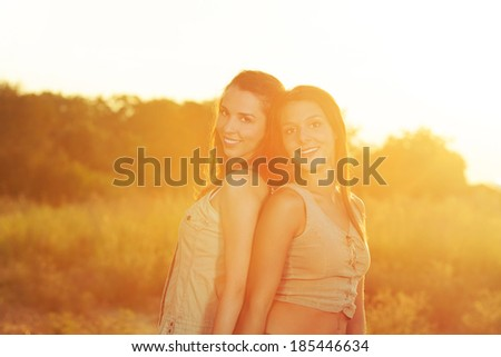 Two beautiful women portrait on a summer sunset. Toned image.