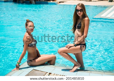 Two beautiful women relaxing at the swimming pool - stock photo