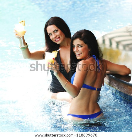Two beautiful women relaxing in swimming pool with cocktails - stock photo