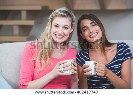 Two beautiful women sitting side by side on sofa with a mug of coffee