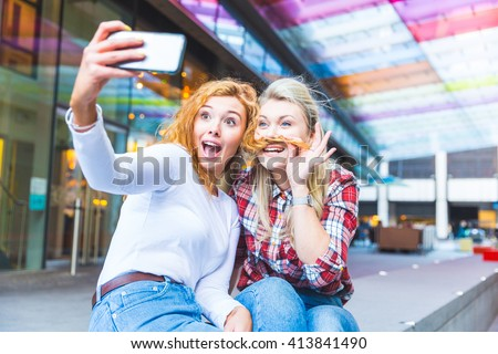 Two beautiful women taking a selfie with funny faces. They are a couple, one blonde and one redhead, looking at smart phone and grimacing. Happiness, togetherness and lifestyle concepts.