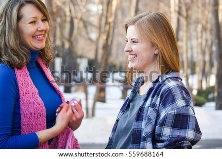 Two beautiful women talking and laughing on the street in the cold season