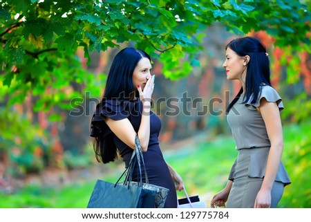 two beautiful women talking in colorful park