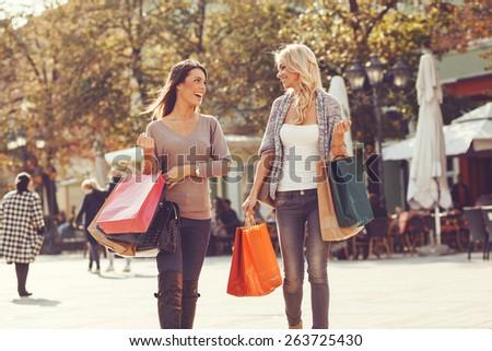 Two beautiful women walking down the street after shopping - stock photo