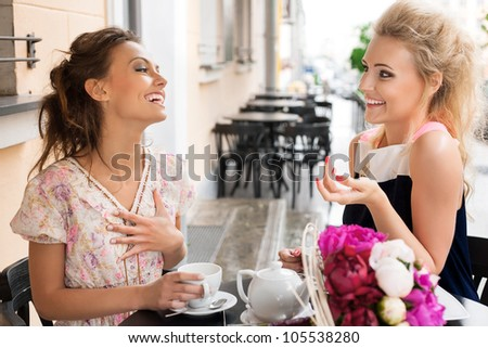 Two beautiful women with great smile and hairstyle sitting at a bar, drinking tea and coffee. - stock photo