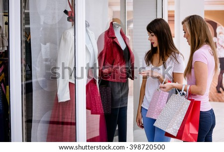 Two beautiful women with shopping bags window shopping in mall - stock photo