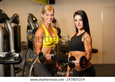 Two beautiful women working out with dumbbells in fitness - stock photo