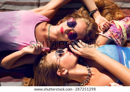 Two  beautiful  young best friends  lying   on  on the   beach and   having fun . Wearing trendy color swimwear and bright sunglasses.  - stock photo