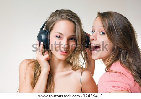 Two beautiful young brunette teens with exuberant expression and a headphone. - stock photo