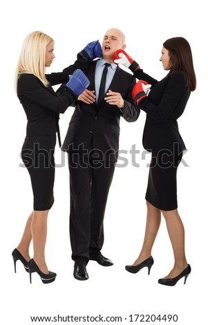 Two beautiful young business women punching boss in the head with boxing gloves - stock photo