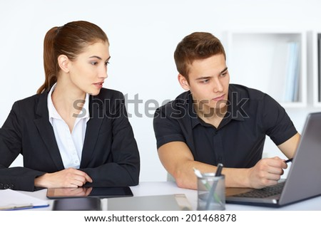 Two beautiful young businesspeople sitting at table in office and looking at laptop computer screen - stock photo
