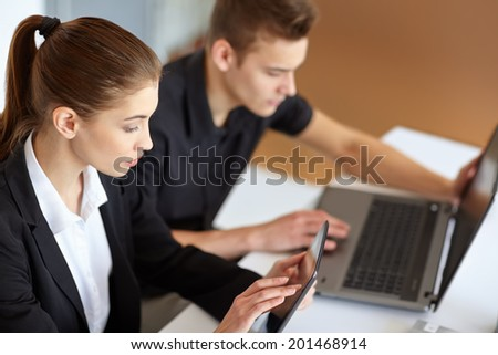 Two beautiful young businesspeople sitting at table in office and working at laptop and tablet pc - stock photo
