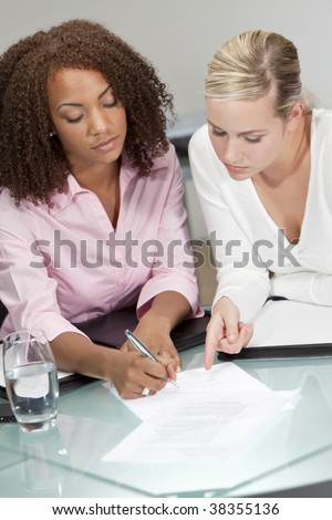 Two beautiful young businesswomen or lawyers, one African American one caucasian, discussing and signing a contract or legal document - stock photo