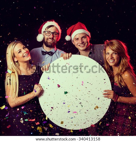 Two beautiful young couples having fun at New Year's Eve party, holding a blank cardboard circle - stock photo