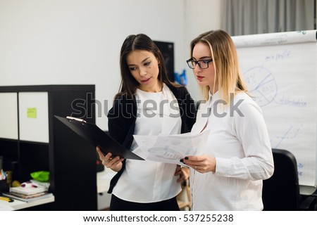 Two beautiful young executives reading some papers