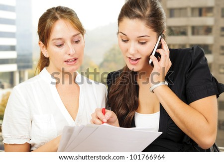 Two beautiful young executives reading some papers and one of them is on the phone - stock photo