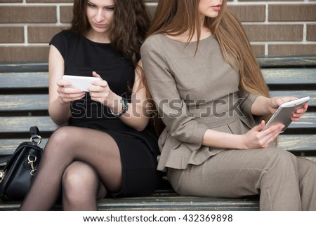 Two beautiful young female sitting side by side on bench without talking and looking at their own devices. Phone addicted attractive caucasian office women ignoring each other. Close-up - stock photo