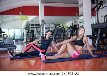 Two beautiful young fit woman stretching legs in the gym