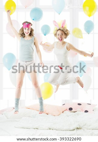 Two beautiful young friends jumping on the bed in sleepwear. pajama party. Cheerful  happy weekend mood. Sunny bedroom with colorful balloons