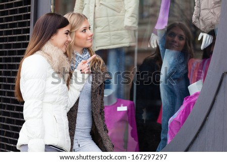 Two beautiful young friends looking about the merchandise