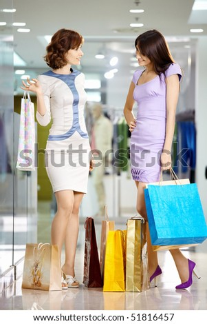 Two beautiful young girls consider the purchases - stock photo
