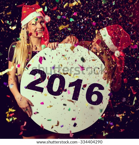 Two beautiful young girls enjoying at New Year's Eve party, holding cardboard circle with 2016 written on it - stock photo