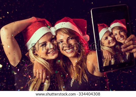 Two beautiful young girls having fun at New Year's Eve party and taking a midnight selfie - stock photo