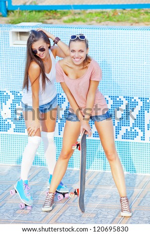 two beautiful young girls in an empty pool, one holding a skateboard, the other wearing roller skates - stock photo
