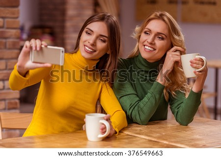 Two beautiful young girls in casual clothes making selfie, drinking coffee and smiling, while sitting in cafe