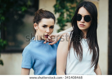 Two beautiful young girls in dresses posing in front of house - stock photo