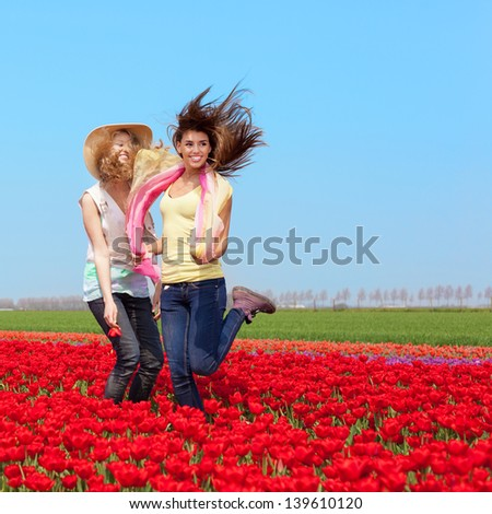 two beautiful young girls jumping in a red tulip field, outdoors - stock photo