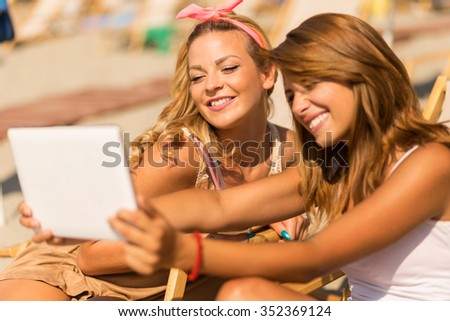 Two beautiful young girls lying on a sunbed on the beach, taking a selfie with a tablet computer - stock photo