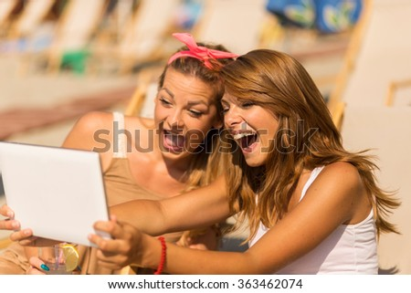 Two beautiful young girls lying on a sunbeds on the beach, taking a selfie with a tablet computer - stock photo