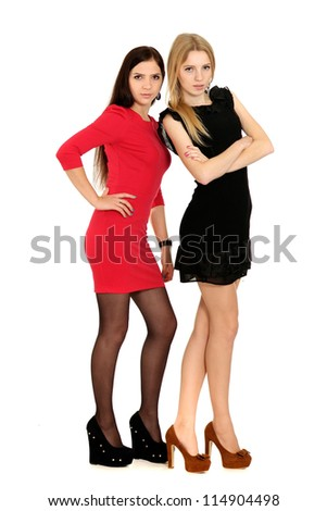 Two beautiful young girls posing on white background - stock photo