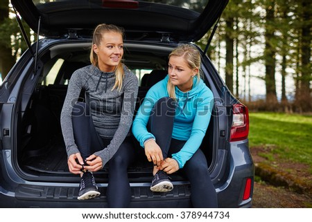 two beautiful young girls preparing for run in back of car, tying shoes - stock photo
