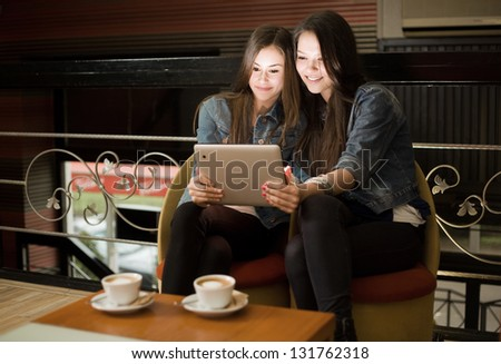 Two beautiful young girls sharing tablet computer.
