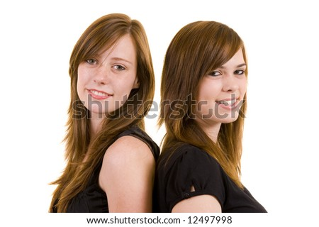 Two beautiful young ladies standing back to back, isolated on white.