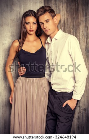 Two beautiful young people in love. Fashionable couple posing at studio.  - stock photo