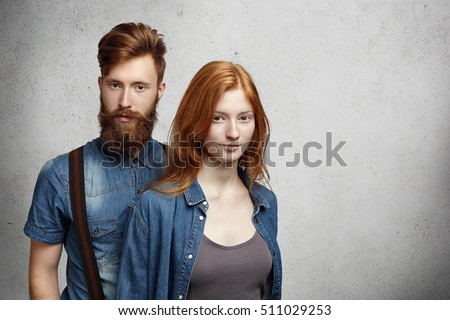 Two beautiful young people posing together in studio. Handsome man with trendy haircut and fuzzy beard relaxing indoors standing close to his attractive redhead girlfriend wearing denim jacket