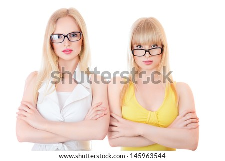 Two beautiful young serious women in glasses isolated on white background - stock photo