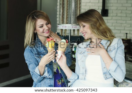 Two Beautiful young woman eating an italian ice cream, selective focus