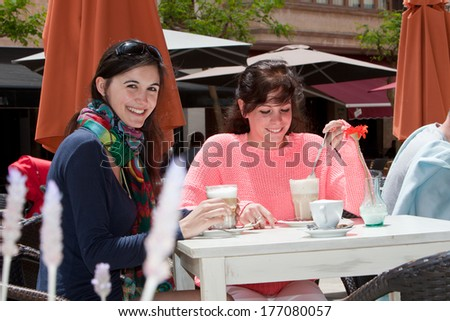 Two beautiful young woman enjoying refreshments at an outdoors restaurant looking up to smile at the camera