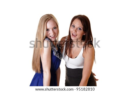 Two beautiful young woman having fun in the studio and laughing, one with blond and the other with brunette hair. - stock photo