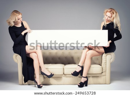 Two beautiful young woman holding empty board. Best friends. - stock photo